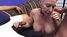 Mature woman with short blonde hair and big tits enjoys two black rods