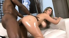 Chubby white babe glistening with oil gets pounded by a black cock